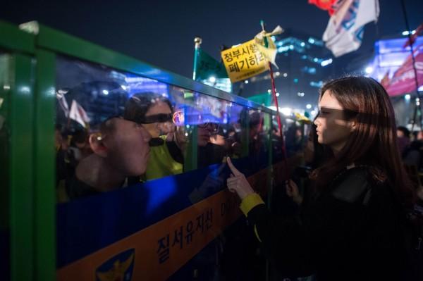 鎮暴警查阻止示威者向總統府前進,雙方發生激烈肢體衝撞,警察還一度噴胡椒噴霧驅離現場的示威者,之後雙方仍隔着圍欄對峙。(法新社)