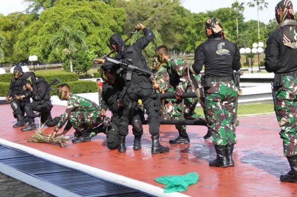 印尼軍拿出活蛇,進行表演。士兵甚至將蛇咬成兩半,並互飲蛇血。(法新社)