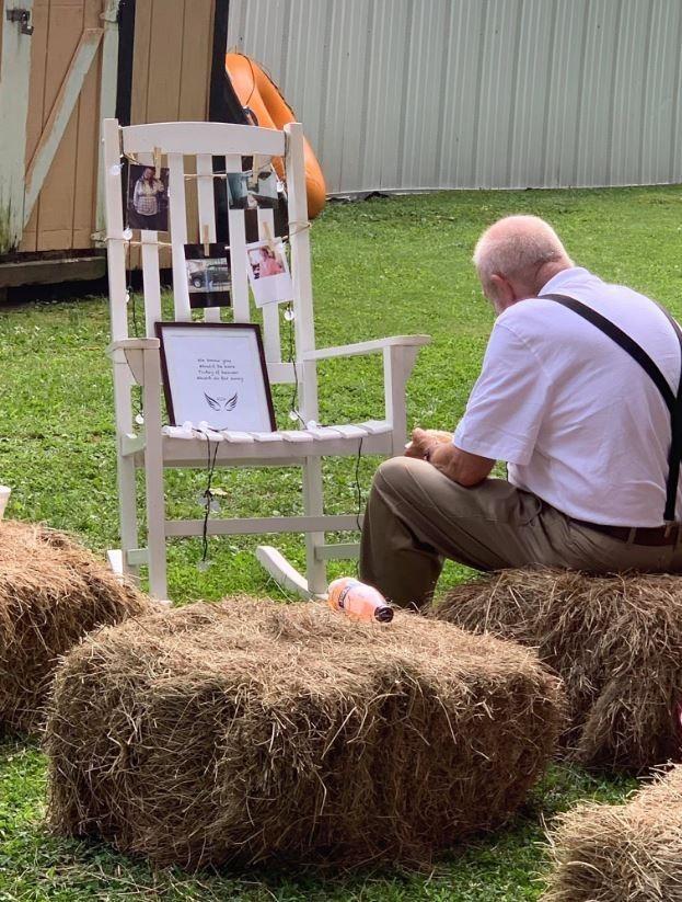 71歲的比利(Billy Gray)獨自坐在「亡者祝福區」,看著亡妻的照片吃飯。(圖取自@sahrahMichelle推特)