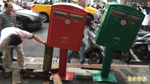 工作人員透過「人工整形」方式,要讓歪腰郵筒再次歪腰。(記者林煙婷攝)