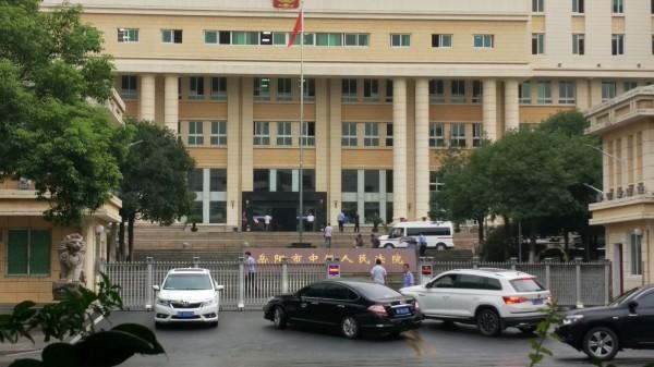 雖然今天是週日,但岳陽市中級人民法院仍有許多車輛進出,更有數名穿著水藍色制服的員警穿梭其中。(中央社)