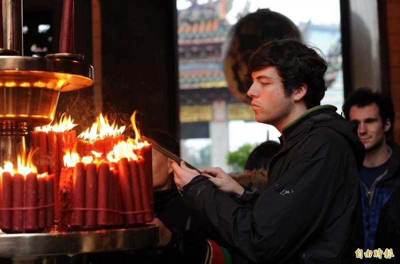 萬華龍山寺香火鼎盛,也是許多觀客必訪的景點,不少外國人造訪時,也會焚燒獻燭祈福。 (記者羅沛德攝)