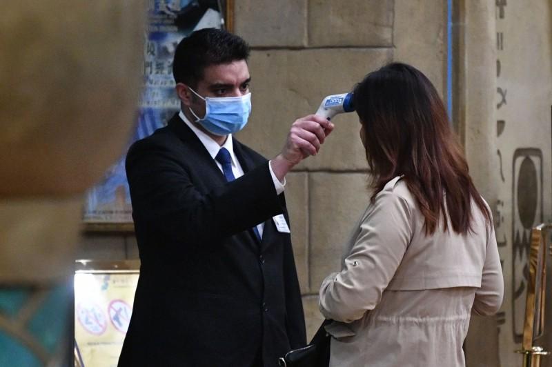 澳門衛生局局長李展潤表示,明日起將舉措讓澳門市民憑身分證購買和衛生局合作的藥房口罩,每人限購10個,市面上的口罩則不做限制。圖為澳門賭場外的體溫檢測。(法新社)