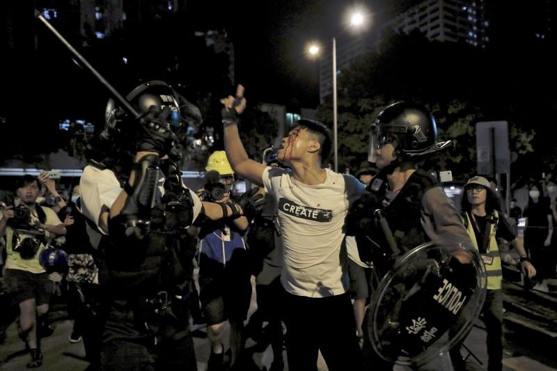 香港葵涌警署外爆發警民衝突,圖為一名支持警方的白衣男子不斷與在場市民對罵。(美聯社)