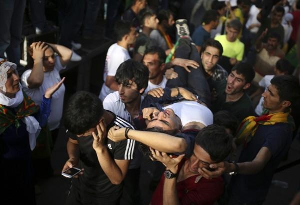 土耳其國會大選的造勢活動發生爆炸案,傷者被群眾抬出。(美聯社)