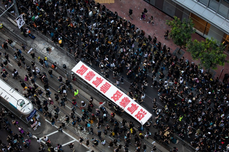參加遊行的民眾認為,沒有中國的暴政就不會有官方口中的「暴民」。(彭博)