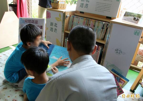 張姓收容人看到孩子一直待在閱讀區不走,嘴巴上念著「讀冊嘸用」,但還是坐下來陪孩子閱讀,場面溫馨。(記者林欣漢攝)