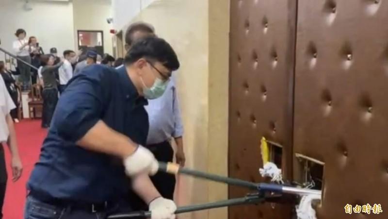 民進黨立委賴瑞隆在門口要剪掉鐵練時,藍委在議場內不斷伸出棒子攻擊。(立委林楚茵提供)