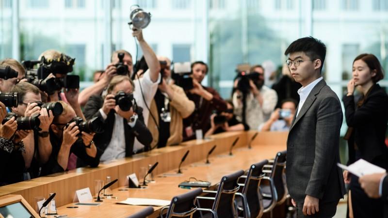 香港眾志秘書長黃之鋒在民間人權連線副召集人黃奕武、旅居漢堡的港人鄺頌晴的陪同下,今天一同出席柏林平日舉行政府例行記者會的聯邦記者會。(歐新社)