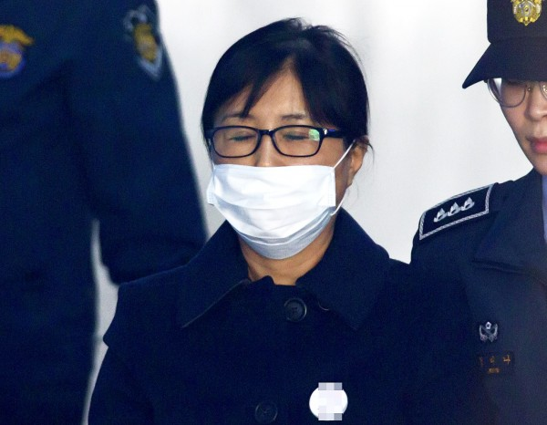 Choi Soon-sil, center, arrives for sentencing in a corruption case linked to ousted former South Korean president Park Geun-hye at the Seoul Central District Court yesterday. Photo: EPA