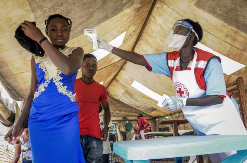 世界衛生組織(WHO)今(17)日通報烏干達出現新的「輸入性」病例,一名剛果漁民越境販魚,在市場多次嘔吐,返回剛果後死於伊波拉病毒感染。圖為防疫人員在剛果與烏干達邊境進行檢疫工作。(美聯社)