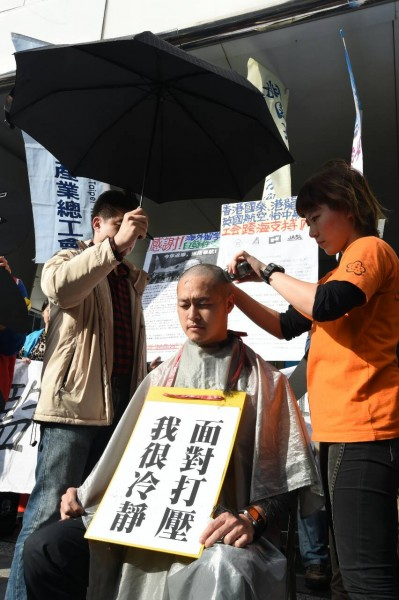 華航一空服員張書元當場落髮剃光頭抗議、還由前同事撐傘、象徵「無髮無天」。(記者廖振輝攝)