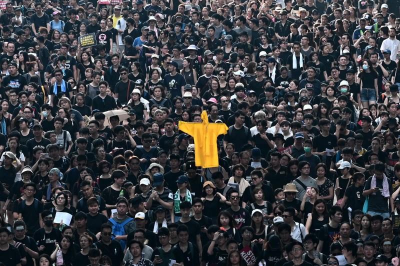 遊行隊伍中出現多件黃色雨衣向「黃衣人」致敬。(法新社)