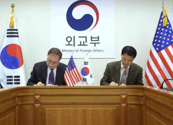 美國談判代表貝茨(右)與南韓談判代表張元三(左)在一份短期協議上簽字。(美聯社)