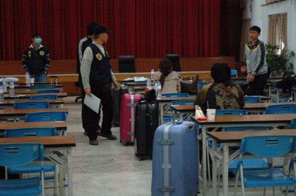 刑事局自斯里蘭卡引度94名台籍詐欺犯,嫌犯一下飛機就拎著行李,被帶往屏東縣警局偵訊。(記者黃良傑攝)