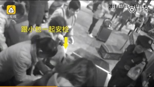 中國女子因不放心隨身財物丟失,連人帶包鑽入安檢機。(圖擷取自梨視頻影片)