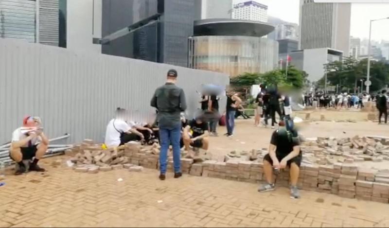 為了鞏固防線,有抗議民眾就地取材,直接將人行道磚頭一塊塊鑿起,砌成城牆。(圖擷自「香港警察 Hong Kong Police」臉書)