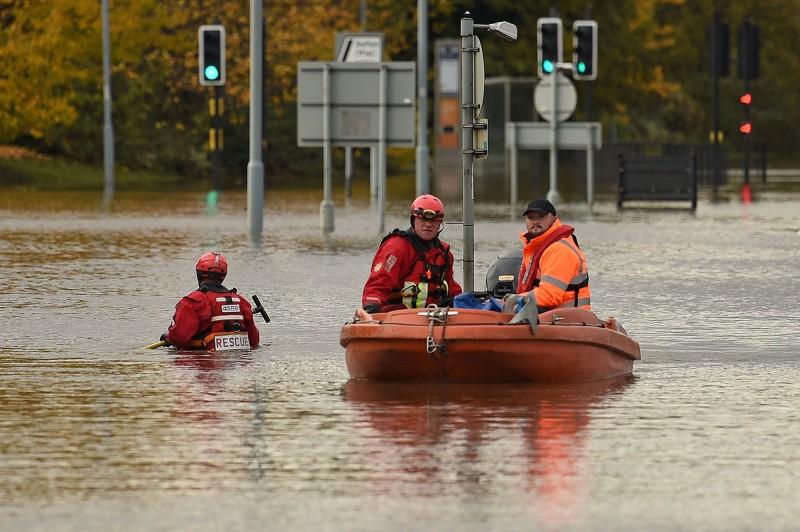 英國英格蘭中部近日發生洪災,救難人員乘膠筏救災。(法新社)