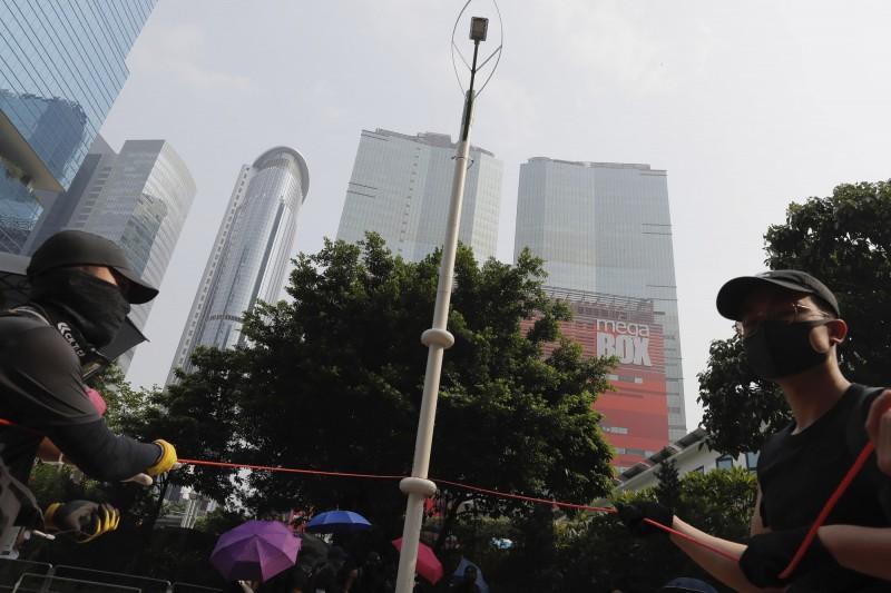 香港示威者今天發起九龍觀塘遊行,除了重申5大訴求,同時反對政府設置智慧燈柱。過程中,示威者試圖拉倒其中一支燈柱。(美聯社)