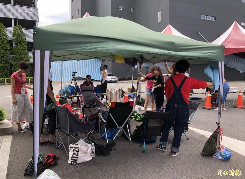 罷工空服員以人身固定支架,以防帳篷被吹翻。(記者魏瑾筠攝)