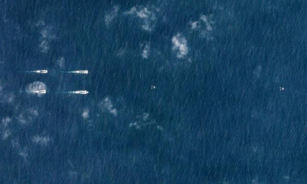 路透社根據衛星畫面獨家報導,中國本週出動至少40艘海軍艦艇與遼寧號航空母艦,在海南島外的南海區域以行列編隊航行。(路透)