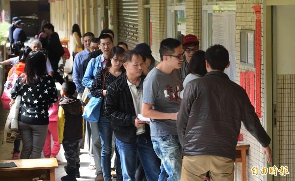 下午開始,不少港、湖地區民眾前往住家附近投開票所排隊投票。(記者廖振輝攝)