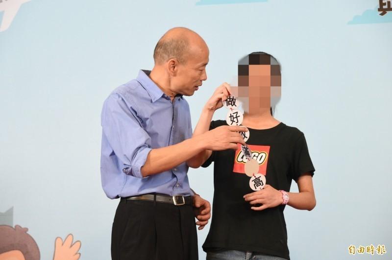一名中華藝校李姓畢業生,在合影時拿出「做好做滿愛高雄」字聯,韓國瑜看完後表情略顯尷尬,要她先收起來。(記者張忠義攝)