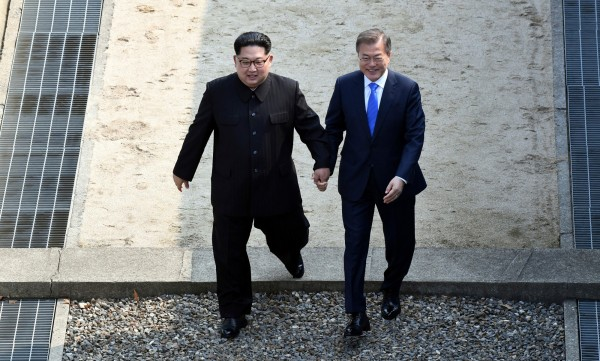 金正恩與文在寅在南北韓軍事分界線碰頭後,將文在寅「牽回」北韓界線內,第一時間引發外界討論。(美聯社)