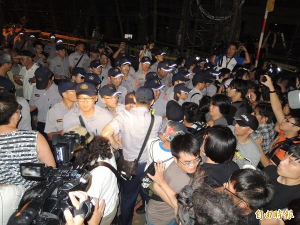 反黑箱課綱學生翻牆攻佔教育部,並佔領部長辦公室,警方逮捕33人,其中包含3名記者。圖為聲援學生凌晨群聚在教育部外,與維安警力爆發嚴重推擠。(記者黃立翔攝)