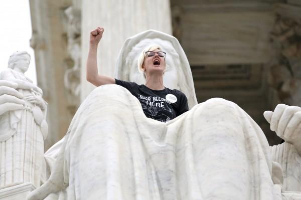 卡瓦諾經參議院投票通過,成為美國最高法院大法官,卡瓦諾宣誓就職的同時,一位女性抗議者爬上最高官法院的「正義女神」尖叫。(路透)