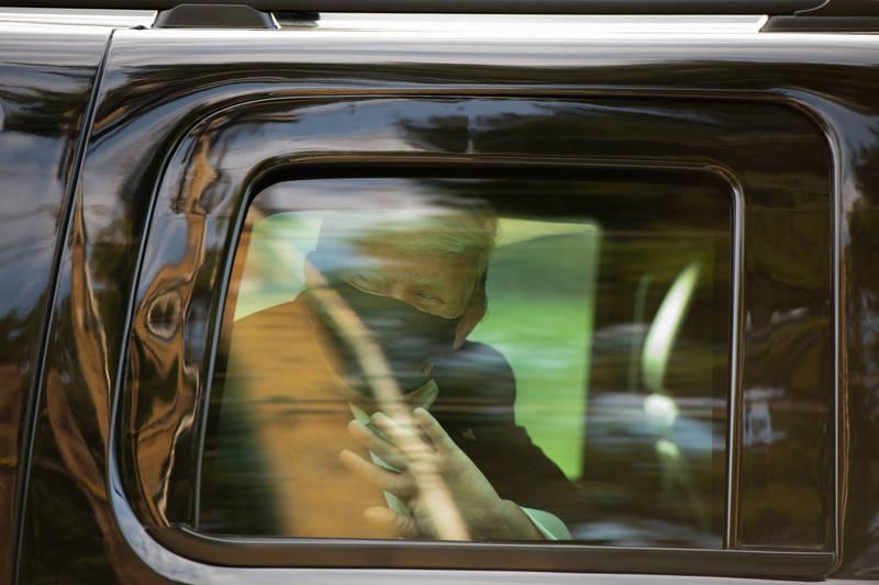 川普短暫離院,乘車向醫療中心外的支持者揮手致意。(彭博)