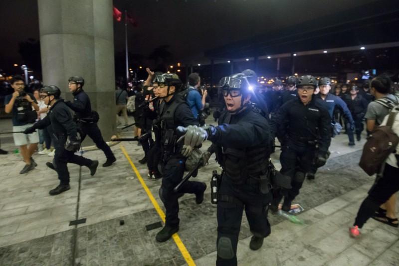 身著防暴裝備的警察在立法會外面對示威者。(彭博)
