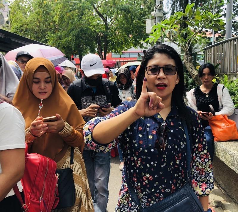 印尼將在4月17日舉行總統及國會大選,海外投票提前於14日開跑。圖為在台灣投完票的印尼民眾大方秀出小拇指,展示代表已投過票的紫色墨水。(中央社)