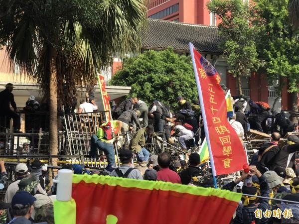 800壯士號召萬人前往抗議,稍早約下午3時許,在立法院拒馬外大唱軍歌,當唱到「夜襲」時,疑似是800壯士團體準備的突襲信號,突然全員爬過立法院外的拒馬及護欄。(記者黃耀徵攝)