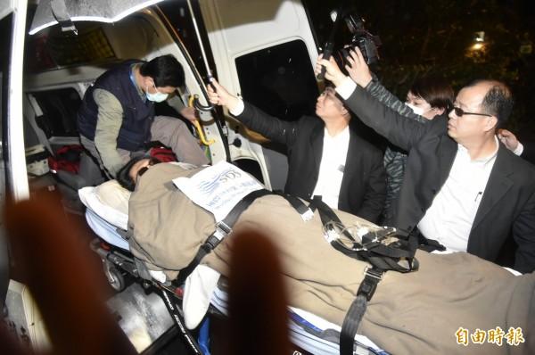 護送黃安進入振興醫院的黑衣人在黃安救護車前等候黃安下車,黑衣人用盡方法遮擋媒體拍攝。(記者陳奕全攝)