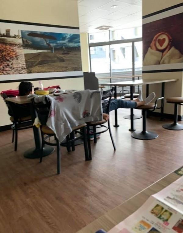 從圖片中可以看到2名學生躺在用餐區的多張椅子上,看起來就像是待在自家一樣舒適。(圖擷自《爆料公社》)