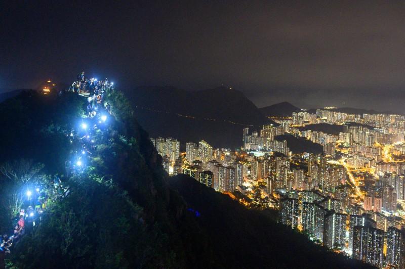 許多香港市民響應活動,自發登上獅子山牽手表達訴求,並亮起手電筒或手機,成為一條圍繞獅子山的光鍊。(法新社)