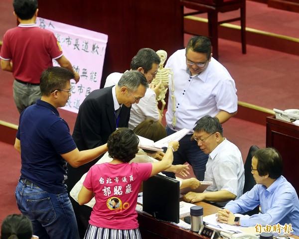 台北市議會16日進行「市長施政報告」,國民黨議員拿道具表達訴求。(記者方賓照攝)