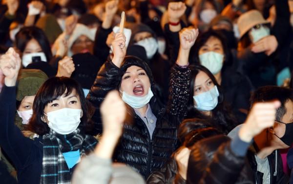 華航工會22日在台北總公司前抗議,許多人都戴上口罩高聲呼口號。(記者張嘉明攝)