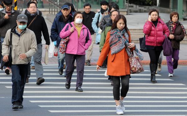 行人步行在斑馬線上,如使用行動裝置容易造成分心而影響交通秩序。(資料照,記者劉信德攝)