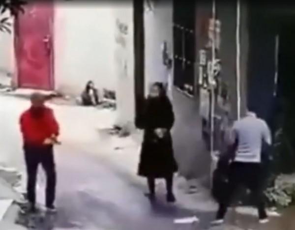 女子看了看嫌犯手上的手槍,接著回頭繼續前行。(擷取自微博)