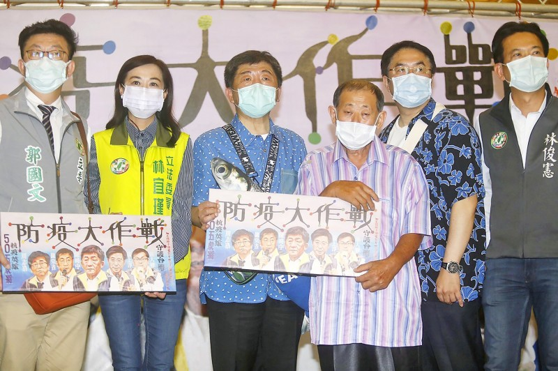 """Minister of Health and Welfare Chen Shih-chung, third left, and other officials in Tainan yesterday hold movie poster-styled prints by painter Yen Chen-fa, third right, with the text """"The great disease prevention war."""" Photo: CNA"""