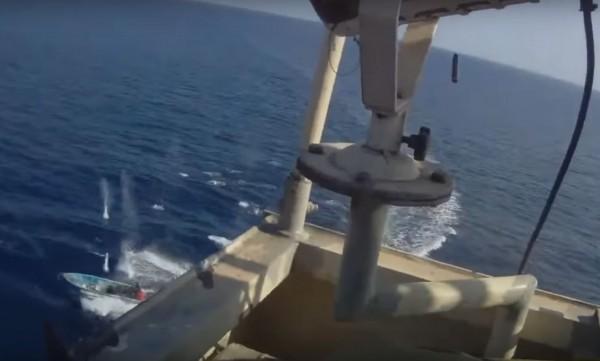 貨輪安保人員朝海盜射擊,海面上被射出許多小水花。(圖擷自YouTube)