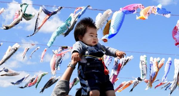 日本微軟推6週帶薪育嬰假,希望藉此讓怕休假薪資減少的男性員工積極地休假。圖為日本小孩。(資料照,法新社)