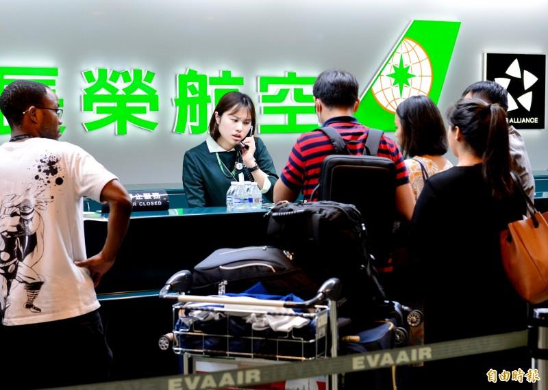 受到罷工影響,桃園機場長榮航空地勤人員忙著幫航班受影響旅客辦理簽轉其他家航空公司航班。(記者朱沛雄攝)