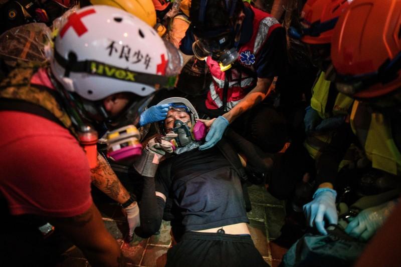 香港昨晚爆發嚴重警民衝突,港警出動武力裝備鎮壓抗爭活動,造成多位港人受傷。(法新社)