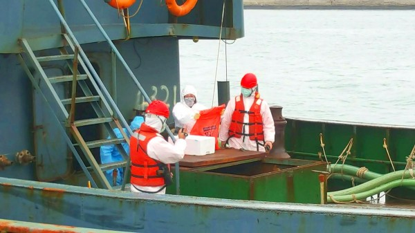 Coast guard members inspect a polystyrene foam box holding 10kg of pork on a Chinese ship that crossed into Taiwan's contiguous zone 23 nautical miles off Penghu County's Cimei Township yesterday. Photo: CNA