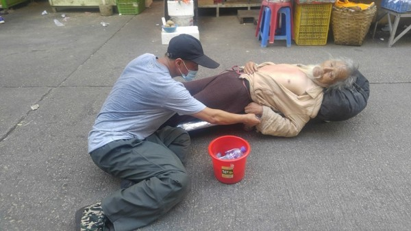 旺角街頭今日驚現兩名行乞男子,一名躺木版,另一名則跪坐在地上,讓網友以為「他要賣身葬父」。(圖擷自「香港突發事故報料區」)