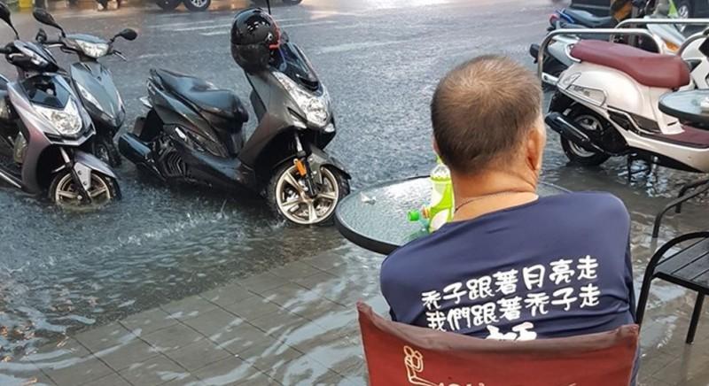韓粉看著淹水的路面,身上還穿著挺韓衣服。(圖擷取自公民割草行動臉書社團)