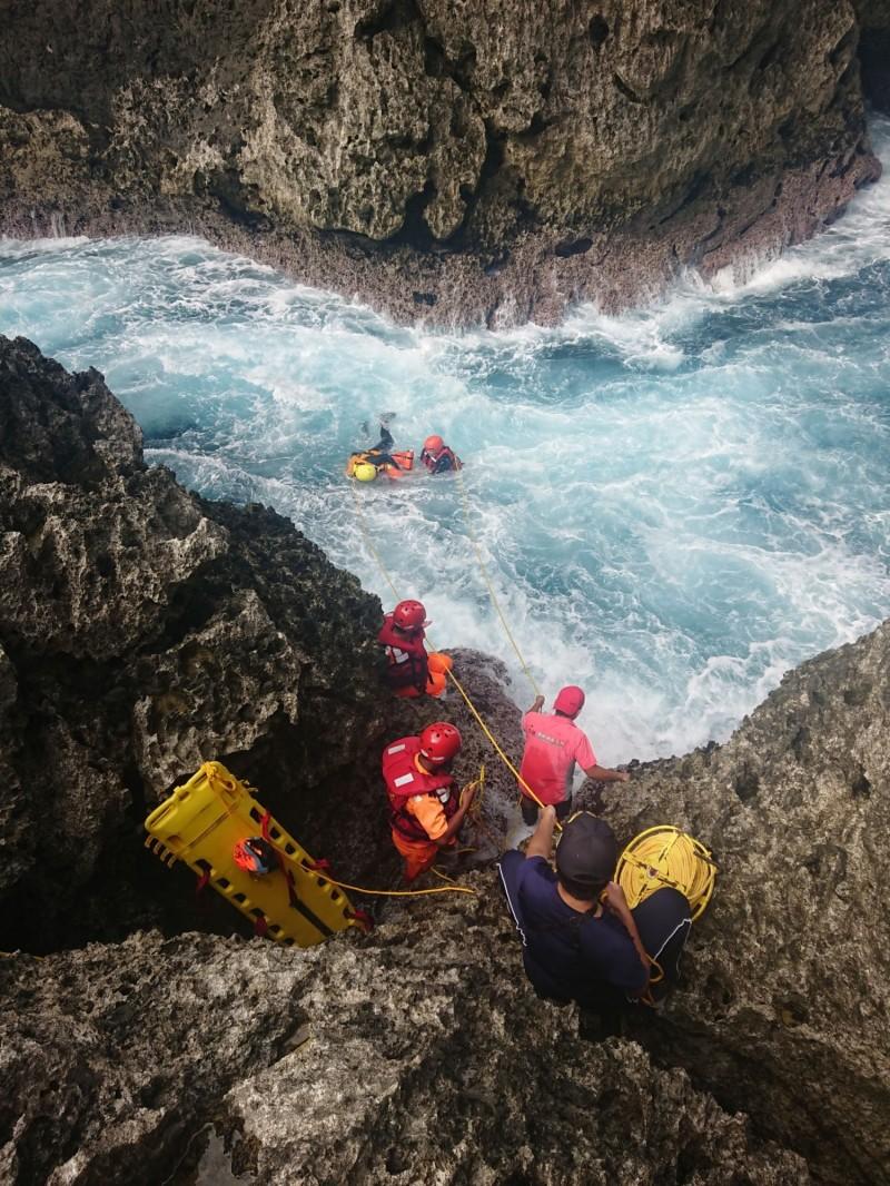 海巡及消防人員合力將漂浮在情人洞附近的溺水者拉上岸。(資料照,記者王秀亭翻攝)